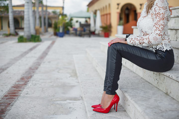 Woman in red high heel shoes sitting on stairs