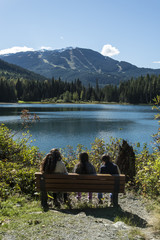 Family on a bench in front of lake in Whistler