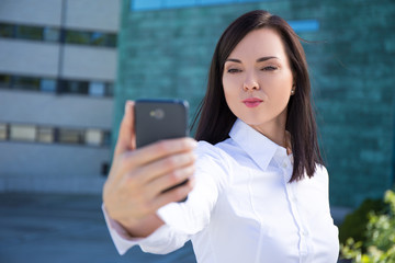 "business woman with ""duck face"" making selfie photo on smartphon"
