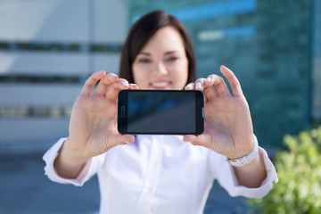 young beautiful business woman showing smartphone with blank scr
