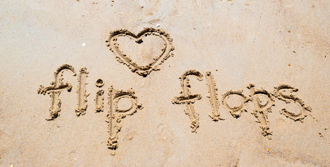 flip-flops handwritten in the sand on the beach with a heart