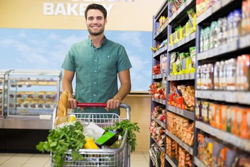 Portrait of smiling man walking with his trolley on aisle