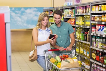 Smiling bright couple buying food products and using notebook