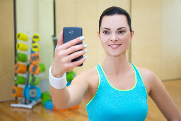 beautiful sporty woman making selfie photo on smartphone in gym