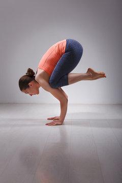 Fit yogini woman practices yoga asana  Bakasana