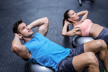 Muscular couple doing abdominal crunch