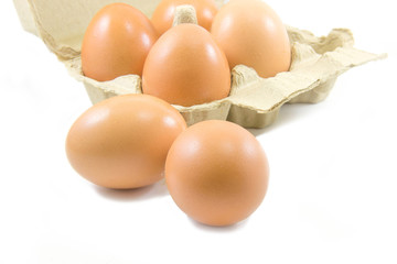 Eggs and paper egg carton on white background