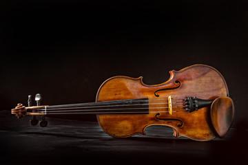 Old violin on dark background.