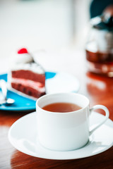 portrait image of cup of tea and cake