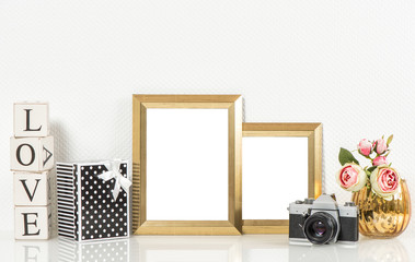 Golden picture frames, roses flowers and vintage camera. Retro d