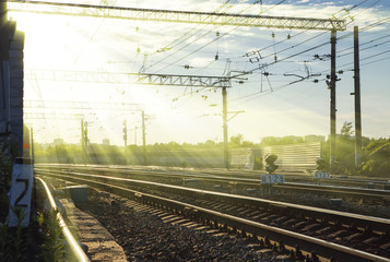 rays of the setting sun over railroad tracks in summer