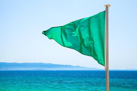 Green flag on the beach over bright blue sea