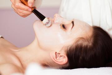 Spa treatment. Beautiful woman with facial mask at beauty salon.