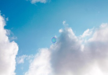 A single bubble against a blue sky with a grey cloud
