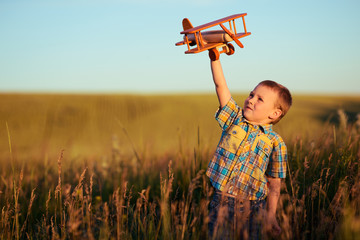small boy playing with plane on meadow