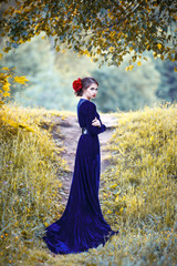 beautiful girl in a long blue dress standing in a half-turn in the park