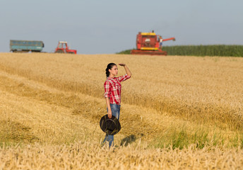 Girl on wheat field during harvest