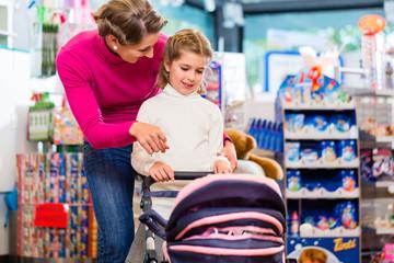 Familie spielt mit Puppenwagen im Geschäft