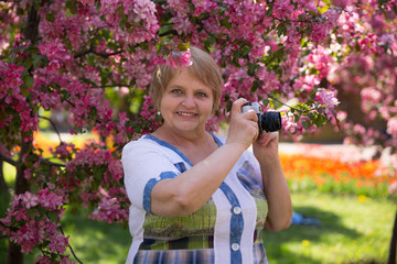 Happy adult woman photographer under pink flowering tree in garden