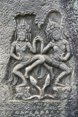 Sculptural relief in stone carving of traditional female goddesses known as apsara dancers at Angkor Wat, Cambodia