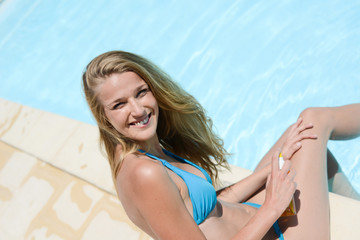 beautiful young woman applying sunscreen protection tan in summertime by the pool