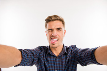 Handsome man making selfie and grimacing
