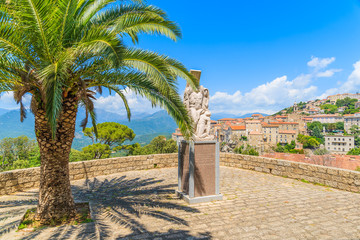 Stone monument and palm tree in Sartene town park, Corsica island, France