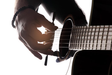 Acoustic guitar close-up with fingers playing it