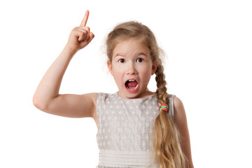 Portrait of excited young girl pointing finger up over white background and looking at camera
