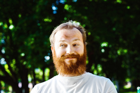 Portrait of happy funny sly mature man with red hair and beard