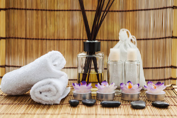 Spa stones, towels and candles shot front on on a bamboo mat and bamboo background