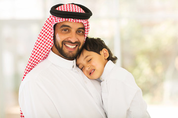 Arabian father holding his sleeping baby
