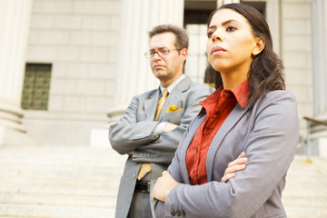 Serious legal or business people on steps with arms crossed looking forward.