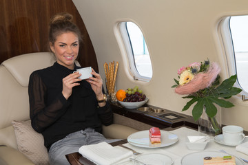 business woman in a corporate jet drinking coffee