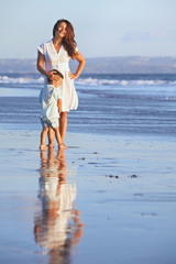 Idyllic portrait with reflection of happy smiling beautiful mother and baby boy on sea beach on background of sunset sky Motherhood, family lifestyle and summer vacation with child on tropical resort
