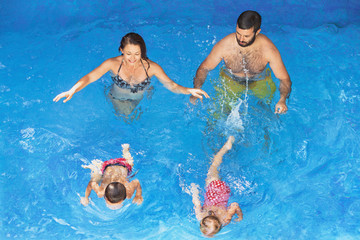 Happy family - father and mother in blue pool with babies girl and boy swimming underwater with fun. Healthy lifestyle, active parents and people water sports activity on summer vacation with children