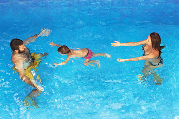 Happy family - father and mother in pool with baby boy swimming underwater with fun. Healthy lifestyle, active parents and people water sports recreational activity on summer holidays with children