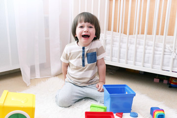 Crying 2 years boy scatters toys at home