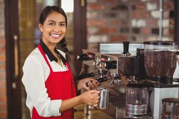 Fototapeta Smiling barista steaming milk at the coffee machine obraz