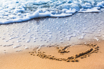 Beach Heart / Drawn heart in the sand at the beach close to the shore