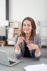 freundliche mitarbeiterin sitzt am schreibtisch im büro