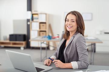 glückliche frau sitzt am schreibtisch im büro