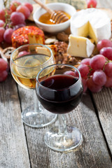 glass of white and red wines, appetizers on a wooden background