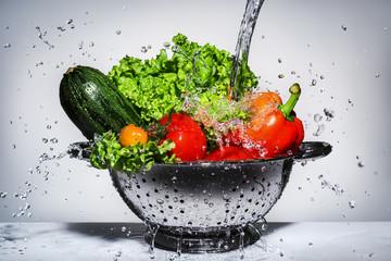 Foto op Plexiglas Groenten vegetables in a colander under running water