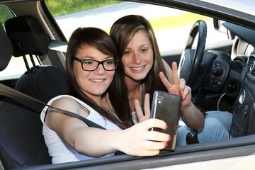 Deux copines se prenant en photo dans une voiture