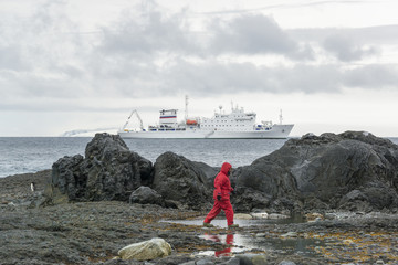 Man walking along rocks by the sea in the Antarctic, the Akademik Sergey Vavilov, a Russian polar research vessel, in the background.