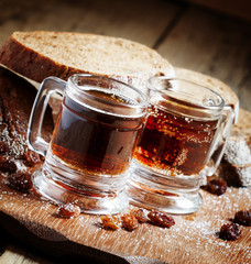 Traditional Russian drink kvass in a mug, with rye bread on a wo