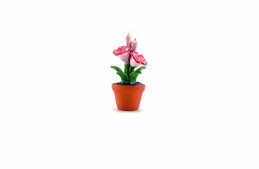 Plastic fake pink flower with brown pot toy isolated on white background