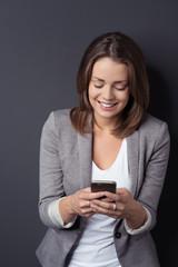 lächelnde frau tippt eine sms auf ihrem smartphone