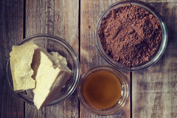 Cocoa butter, cocoa powder and honey on grunge wooden background